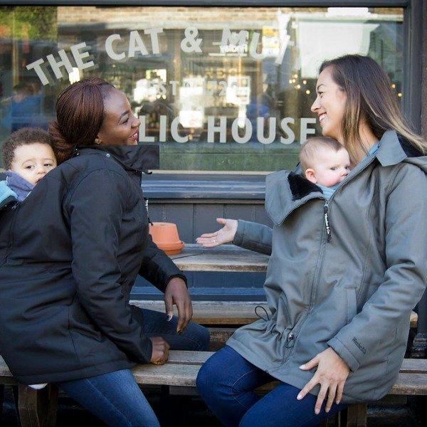 Two women wearing babywearing coats