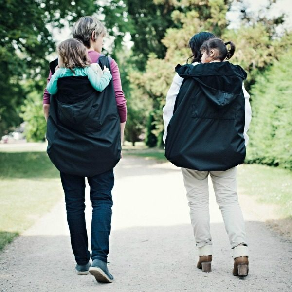 action shot of two parent wearing bundlebean rain covers to keep baby and toddler dry and warm