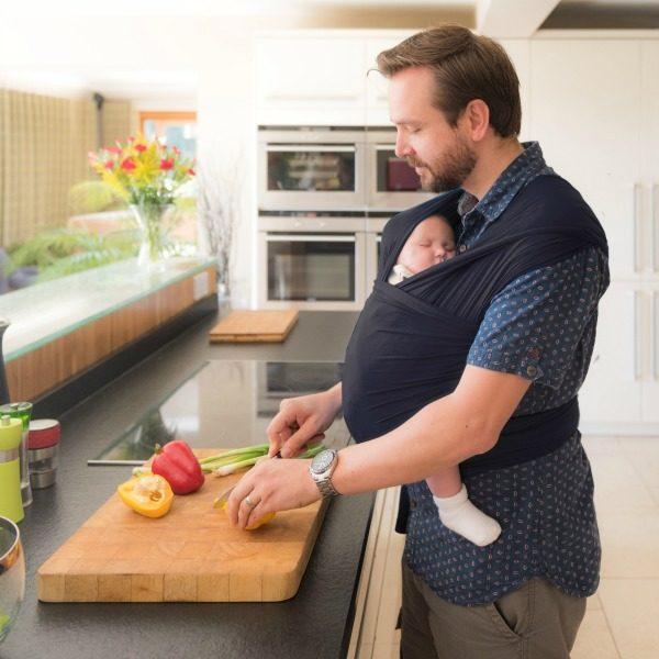 dad preparing food wearing baby in Slate izmi baby wrap bamboo